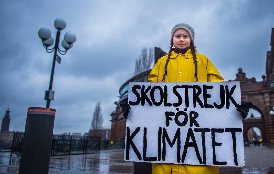 Greta Thunberg holds a placard reading