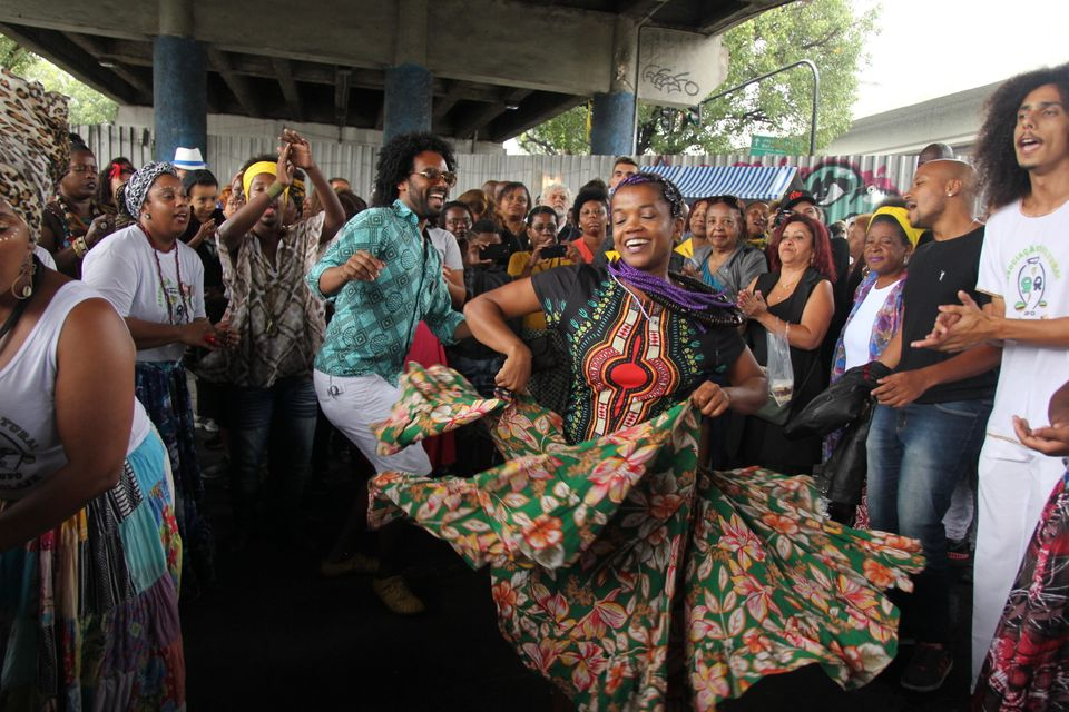 "Brazilians dance in the ""roda do Jongo"" in Madureira under a bridge."