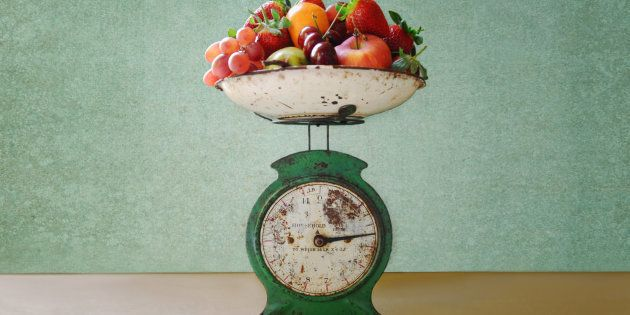 Old vintage kitchen scales laden with strawberries, oranges, pears, cherries, apples and grapes.
