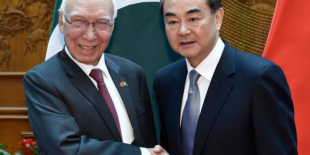 Pakistan Foreign Affairs Adviser Sartaj Aziz (L) shakes hands with Chinese Foreign Minister Wang Yi before...