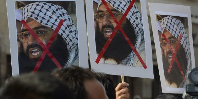 Activists carry placards showing Jaish-e-Mohammad Chief Masood Azhar during a protest against the attack...