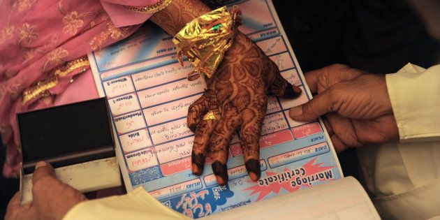 An Indian Muslim bride puts a thumb impression on a Marriage Certificate in the presence of religious...