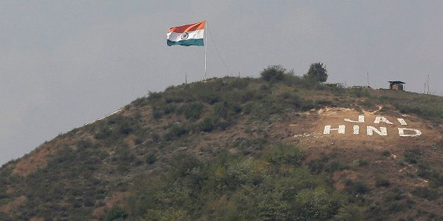The Indian flag flies on a hill in Uri sector, near the de facto border dividing Kashmir between India...