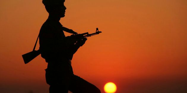 An Indian policeman is silhouetted against the setting sun as he stands guard on the banks of river Tawi...