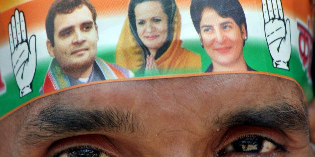 A Congress party worker wears a band on his forehead with pictures of party leaders Sonia Gandhi, Rahul...