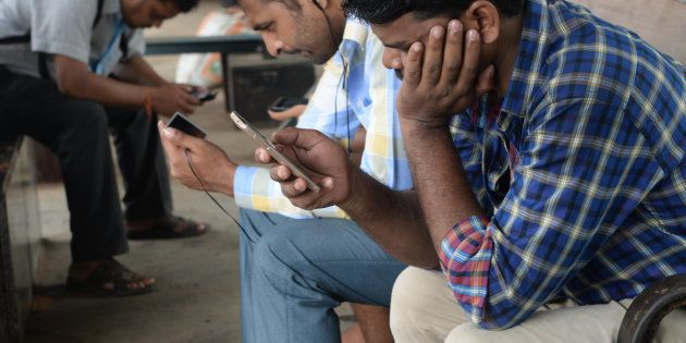 Indians surf the internet on their phones at a free wi-fi zone inside a suburban railway station in