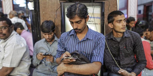Passengers use smartphones while charging the devices at Mumbai Central railway station in