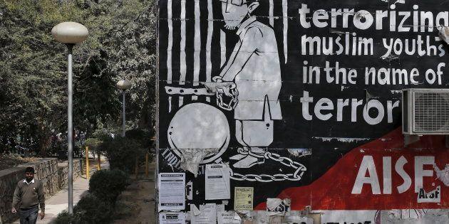 A man walks past graffiti inside the Jawaharlal Nehru University (JNU) campus in New Delhi, India, February...