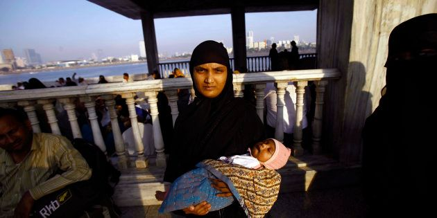 A Muslim woman holds her child and stands at the Haji Ali Dargah in Mumbai, India, Thursday, Nov. 8,