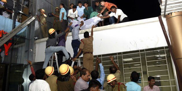 This photograph taken on October 17, shows Indian rescue workers lowering a body of a victim of a massive...
