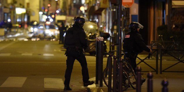 Policemen patrol near the Bataclan Theatre, one of the site of the attacks in Paris on November 15,