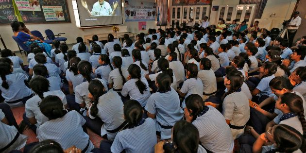 Students in Ahmadabad watch Prime Minister Narendra Modi on screen as he speaks during a nationwide address...