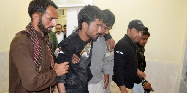 Police help an injured colleague into the hospital after militants attacked the Balochistan Police College...