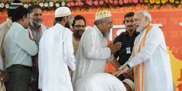 Indian Muslims greetNarendra Modi (R) at the Gujarat University Convention Centre in Ahmedabad on September...