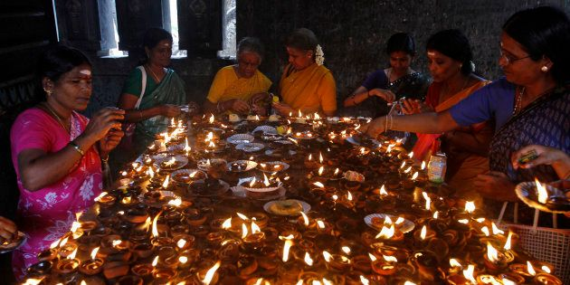 Devotees light earthen oil lamps as they pray to celebrate the Aadi Krithigai festival at a temple in...