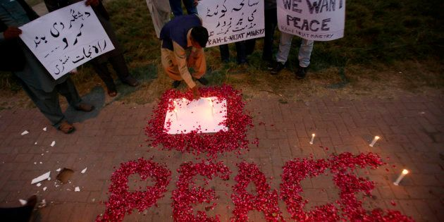 A Christian adjusts a candle next to wording 'Peace' drawn with rose petals during a candlelight vigil...