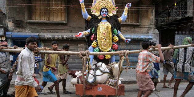 An image of Hindu goddess Kali is carried by workers towards a worship venue, in Calcutta, India, Thursday,...