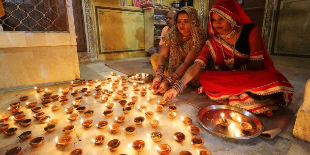 Women light earthen lamps diyas at Ramchandran Ji Temple on the occasion of Diwali in Jaipur, October...