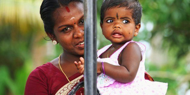 Portrait of young indian mother with a baby girl wearing traditional make-up on their foreheads at Alleppey...