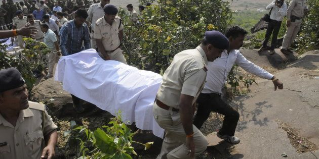 Police personnel carrying the body of SIMI terrorists killed in an encounter at Acharpura on October...