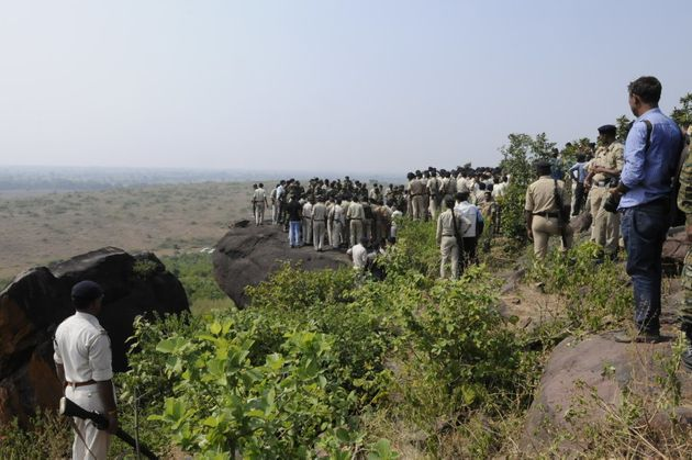 Policemen surround the area where eight SIMI terrorist were killed in an encounter lying on ground at...