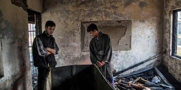 Students inspect the damage of a partially burned government high school in Goripora, on the outskirts...
