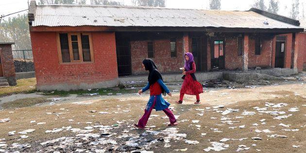 SRINAGAR, INDIA - OCTOBER 31: Girls passing near the burnt building of government school at Gori Pora...