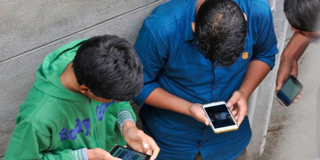 Kashmiri boys surf internet on their phones after hacking into a network during restrictions in civil...