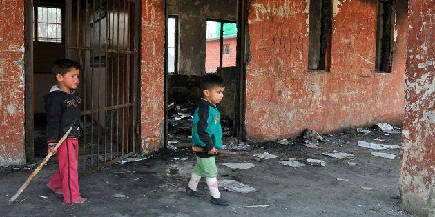 Small children play at the burnt building of government school at Gori Pora on October 31, 2016 in Srinagar,