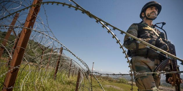 An Indian Army soldier patrols on the fence near the India-Pakistan