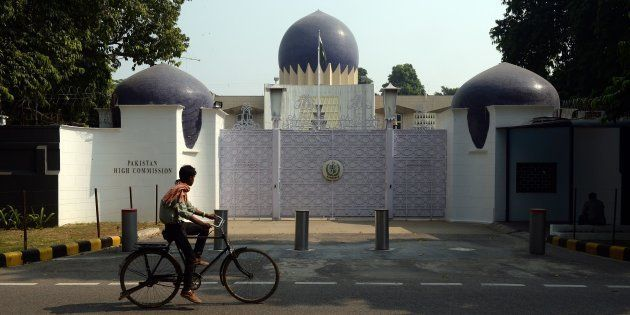 An Indian cyclist rides past the entrance to the Pakistan High Commission in New