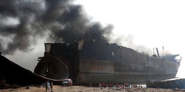 Rescue workers gather near the burning oil tanker at the ship-breaking yard in Gaddani, Pakistan, November...