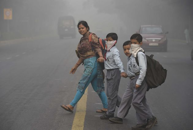 School children battling the haze of contaminated air early in the morning on their way to