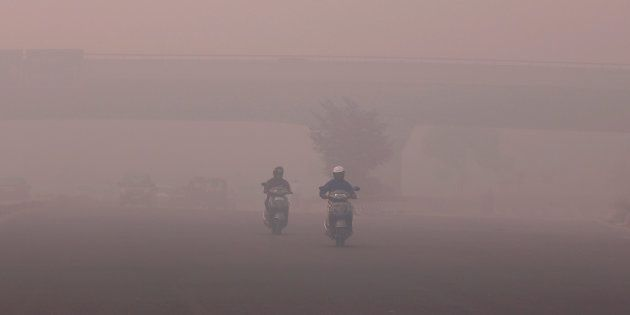 Commuters make their way amidst the heavy smog in New Delhi, India, October 31,