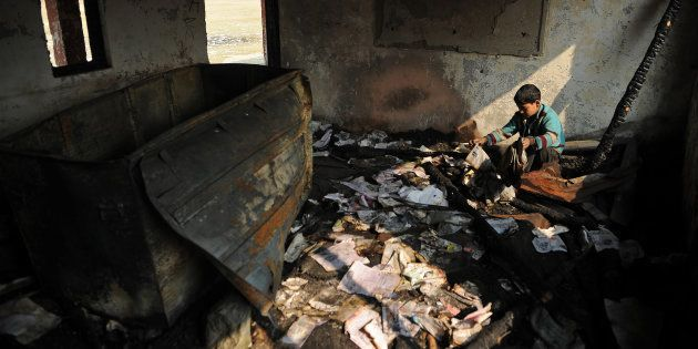 A Kashmiri student looks at damaged property at a partially burnt government high school in Goripora,...