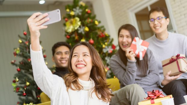 close up on christmas pine tree branch with decoration and group of diverse friends holing glass and cheers for celebrate in living room at home , xmas and happy new year party concept