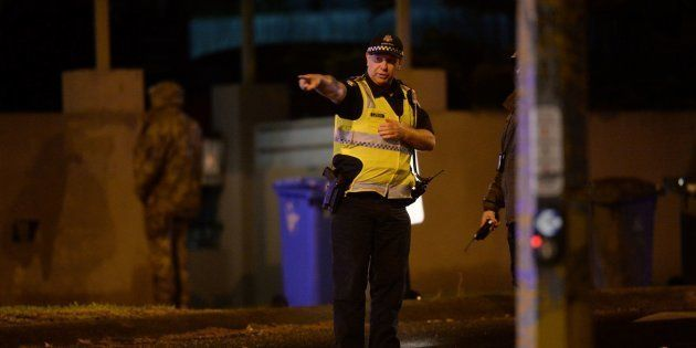 An armed police officer at the scene in the Melbourne bayside suburb of Brighton on Monday