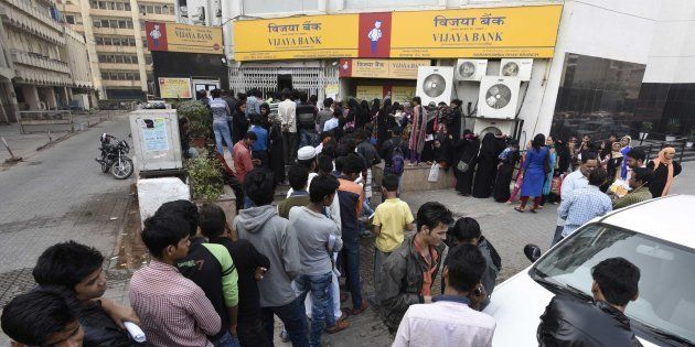 NEW DELHI, INDIA - NOVEMBER 24: People stand in a queue outside banks to deposit and exchange old denomination...
