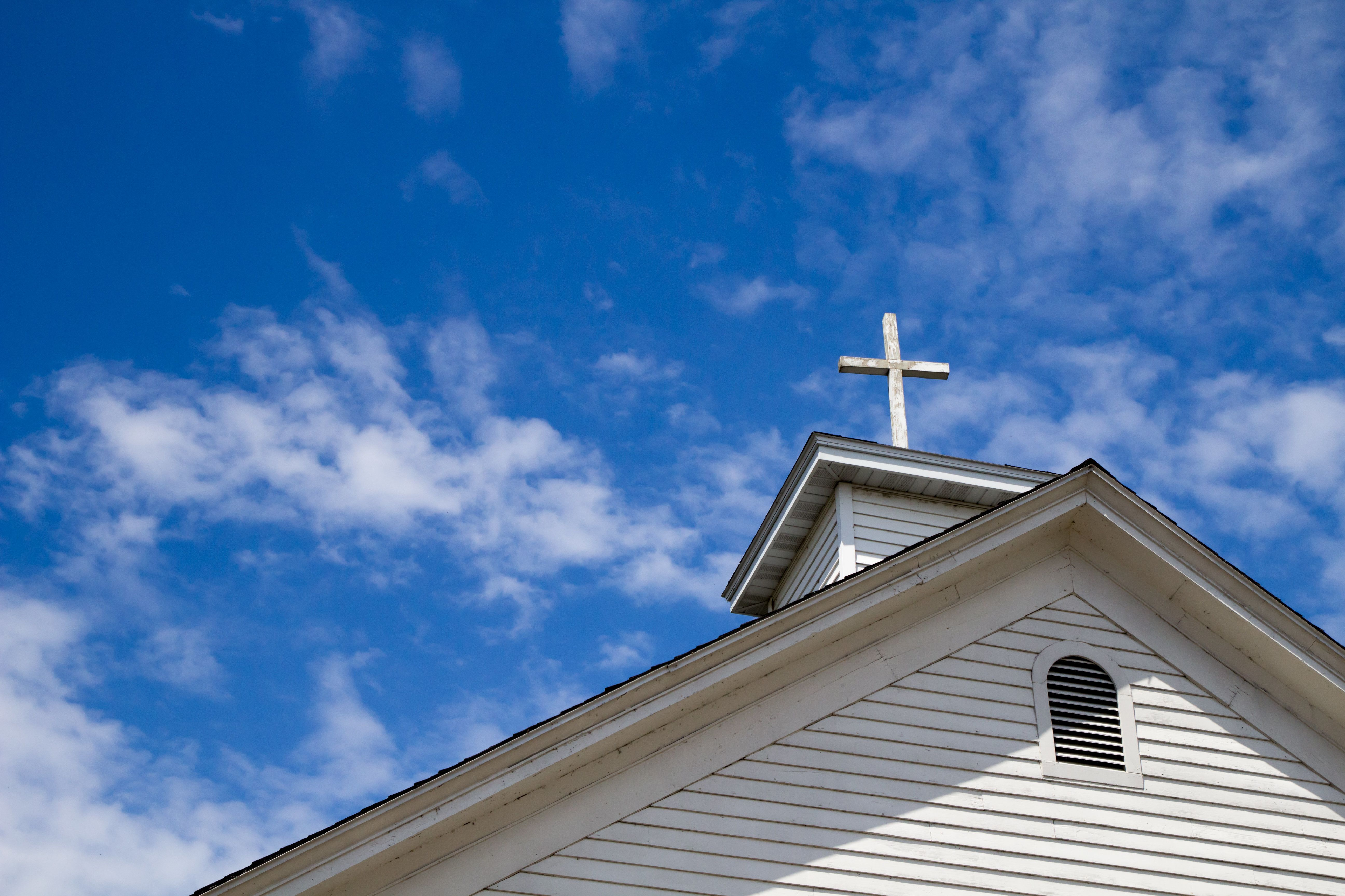 Wooden cross on a simple steeple set against a sunny summer blue sky.