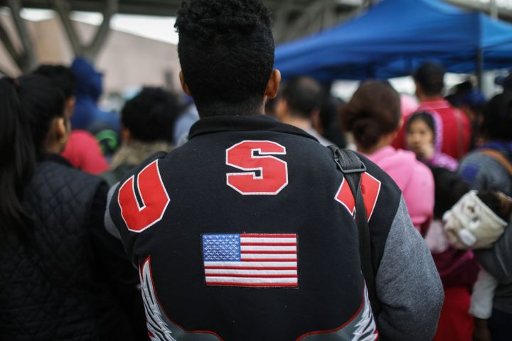 "A man in a ""USA"" jacket waits with migrants at the El Chaparral border crossing to hear names called out on Nov. 28."
