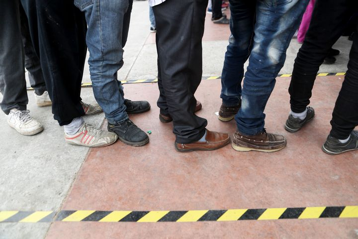 Migrants wait in a plaza at Tijuana's El Chaparral border crossing to place their names on a list to be allowed to cross into