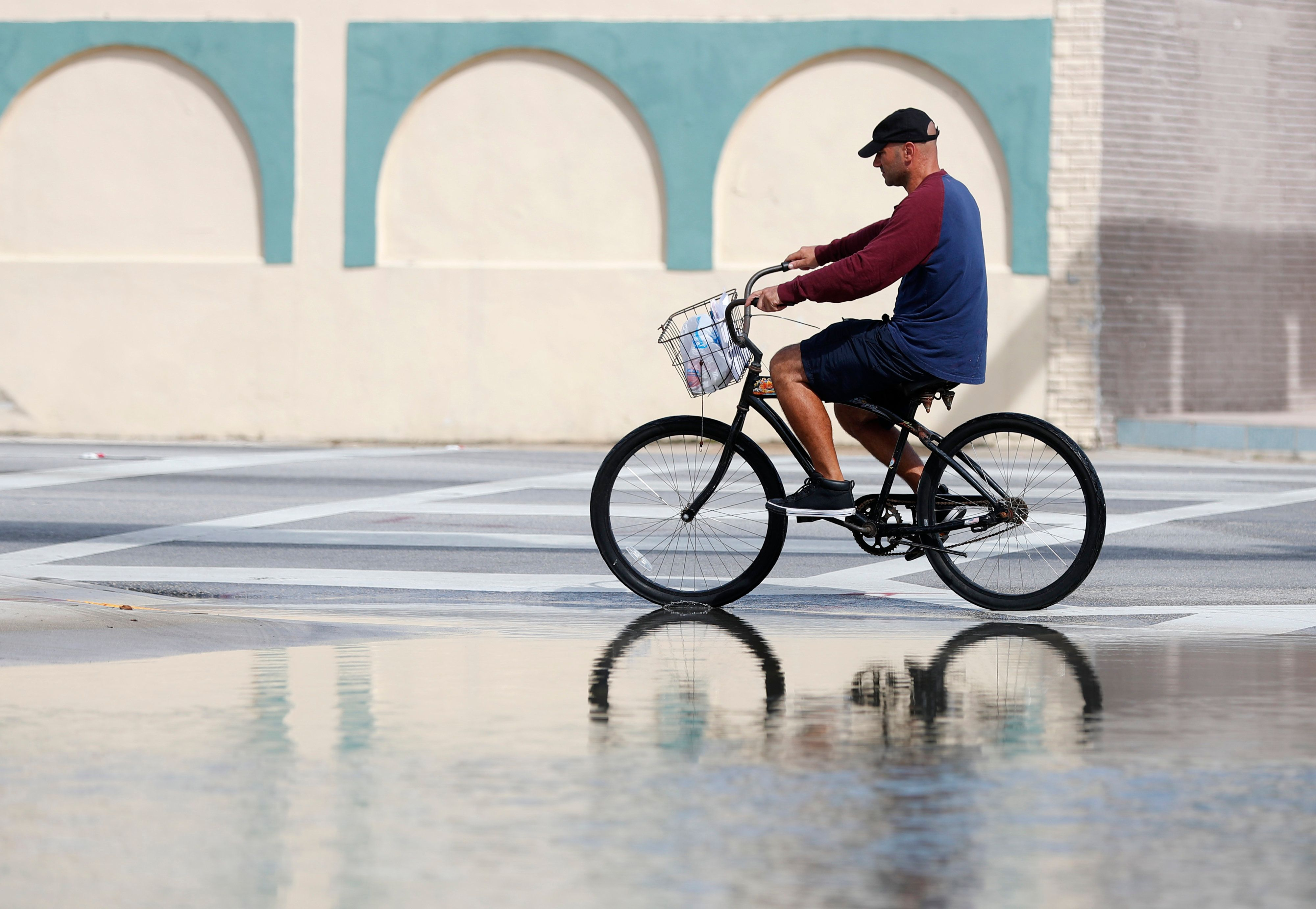 A cyclist in Miami rides past an area flooded during a king tide, an especially high tide, on Oct. 9, 2018.