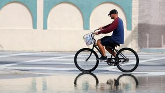 A cyclist rides past an area flooded during a King Tide, an especially high tide, Tuesday, Oct. 9, 2018, in Miami. (AP Photo/Wilfredo Lee)