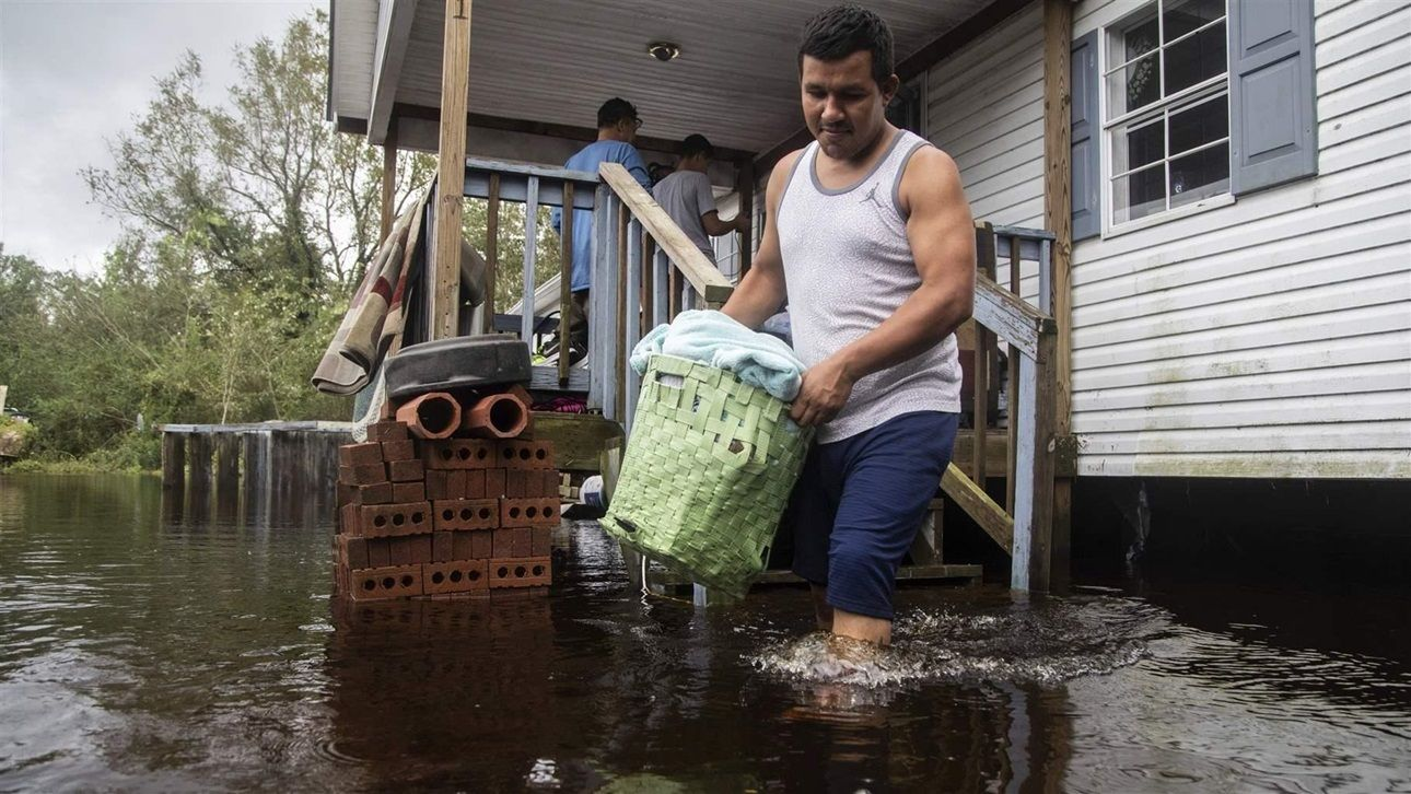 A man helps his family move out of their flooded home in Kinston, North Carolina. Hurricane Florence flooded the Neuse River and devastated the town.