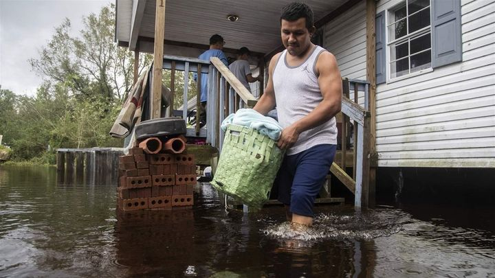 A man helps his family move out of their flooded home in Kinston, North Carolina. Hurricane Florence flooded the Neuse River