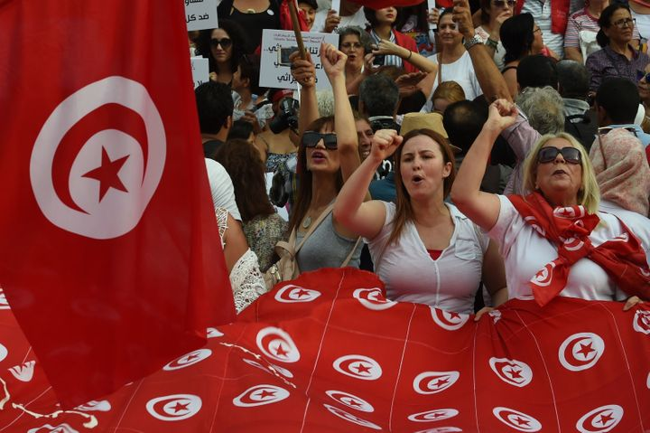 Tunisian women chant slogans and wave their national flags during a demonstration to mark Tunisia's Women's Day o