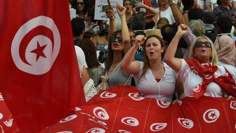 Tunisian women chant slogans and wave their national flags during a demonstration to mark Tunisia's Women's Day and to demand equal inheritance rights between men and women on August 13, 2018, in the capital Tunis. - Tunisia's President Beji Caid Essebsi announced plans to submit a draft bill to parliament equalising inheritance rights between men and women. The proposal to equalise inheritance is among the most hotly debated of a raft of proposed social reforms, guided by a commission the president set up a year ago. (Photo by FETHI BELAID / AFP)        (Photo credit should read FETHI BELAID/AFP/Getty Images)