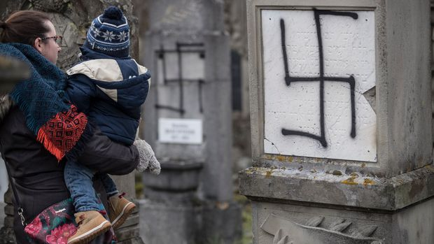 A woman and her child watch defaced gravestones at the Jewish cemetery of Herrlisheim, near Strasbourg, eastern France, Friday, Dec.14, 2018. 37 gravestones and a monument for Holocaust victims have been tagged with anti-Semitic graffiti. The graffiti that include Nazi symbols were discovered on Tuesday, hours before a gunman sprayed gunfire near the Christmas market of Strasbourg. (AP Photo/Jean-Francois Badias)
