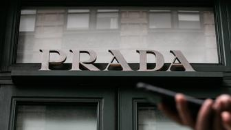 A pedestrian uses a mobile device while passing in front of a Prada SpA store with white shades covering its window displays in New York, U.S., on Friday, Dec. 14, 2018. Prada SpA?will stop selling a $550 monkey figurine after social media users in the U.S. called out a strong resemblance to racist caricatures historically used to dehumanize black people. Photographer: Jeenah Moon/Bloomberg via Getty Images