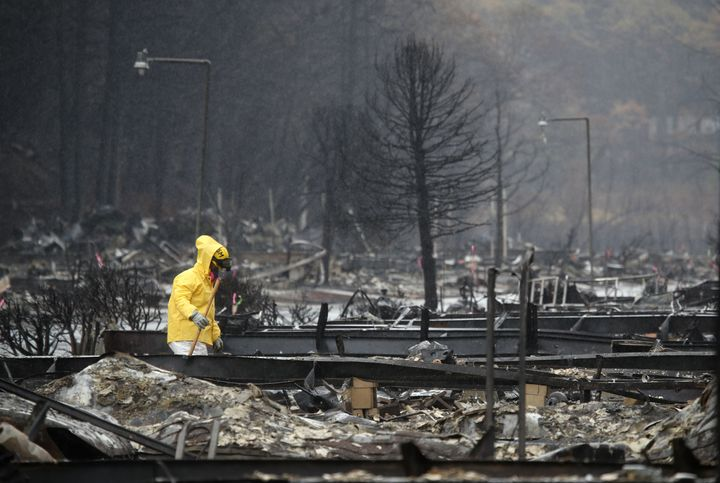 A search and rescue crew member searches for human remains at a mobile home park that was destroyed by the Camp Fire in Calif